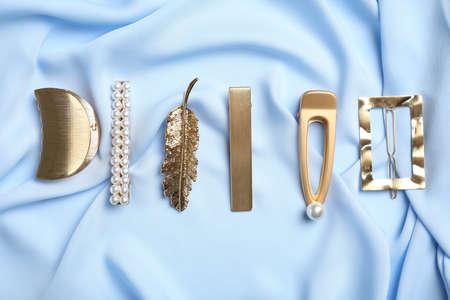 Stylish hair clips on light blue fabric, flat lay Stock fotó