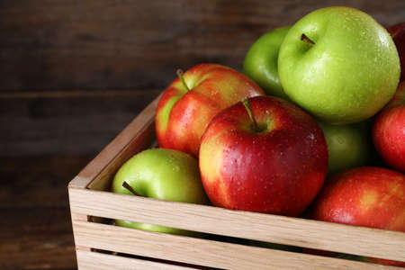 Ripe juicy apples in wooden crate on wooden table, closeup