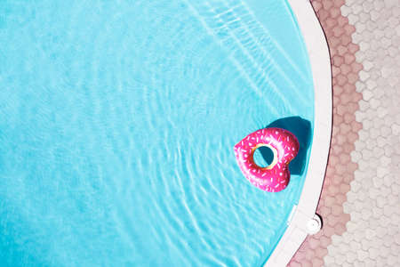 Heart shaped inflatable ring floating in swimming pool, top view with space for text. Summer vacation
