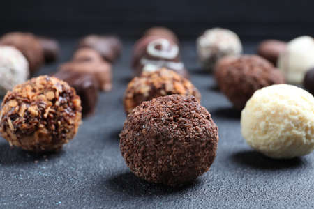 Different tasty chocolate candies on black table, closeup