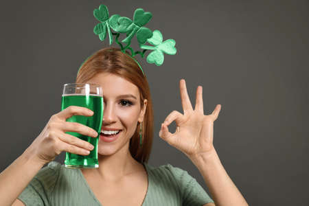 Young woman with clover headband and green beer on grey background. St. Patrick's Day celebration