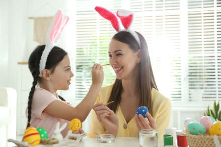 Happy mother and daughter with bunny ears headbands having fun while painting Easter eggs at home
