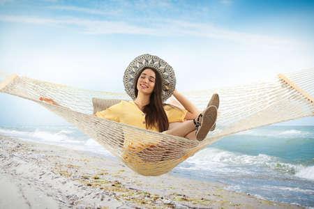 Woman resting in hammock near sea on sunny day Archivio Fotografico