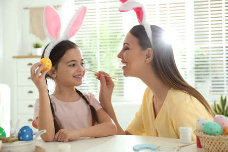 Happy mother and daughter with bunny ears headbands having fun while painting Easter egg at home Banco de Imagens