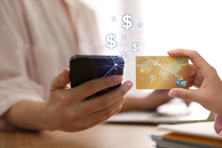 Fintech concept. Woman using phone to make financial transactions with credit card