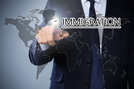 Businessman touching word IMMIGRATION on virtual screen against grey background, closeup Imagens