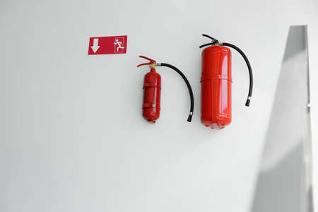 Fire extinguishers and emergency exit sign on white wall indoors Banque d'images