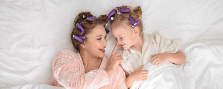 Happy mother and daughter with curlers lying on bed, top view. Banner design