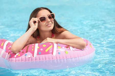 Beautiful young woman on inflatable ring in swimming pool 스톡 콘텐츠