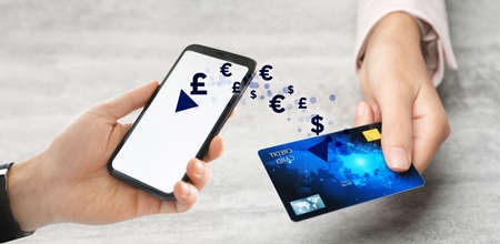 Fintech concept. Man using phone to make financial transactions with credit card