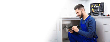 Male plumber with clipboard near kitchen sink, space for text. Banner design Stock fotó