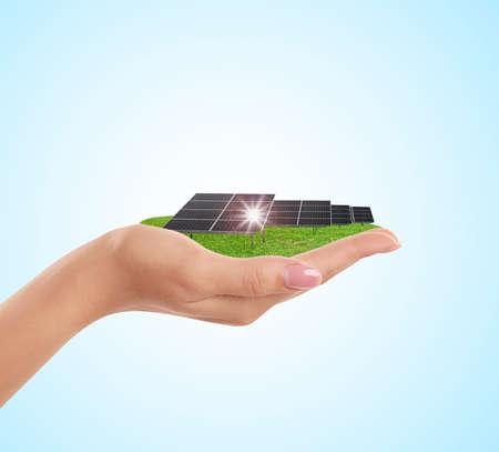 Woman demonstrating solar panel on light blue background, closeup. Alternative energy source