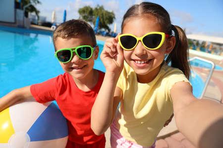 Happy children taking selfie near swimming pool. Summer vacation