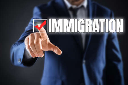 Businessman touching word IMMIGRATION on virtual screen against dark grey background, closeup Imagens