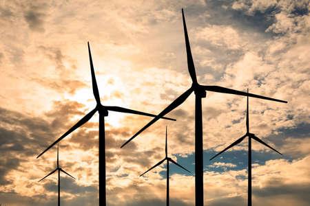 Silhouettes of wind turbines at sunset. Alternative energy source 版權商用圖片