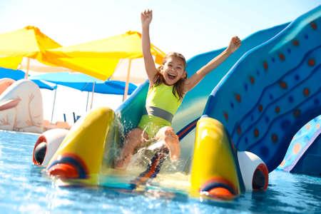 Happy girl on slide at water park. Summer vacation Foto de archivo