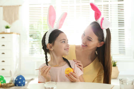 Happy mother and daughter with bunny ears headbands painting Easter egg at home Banco de Imagens