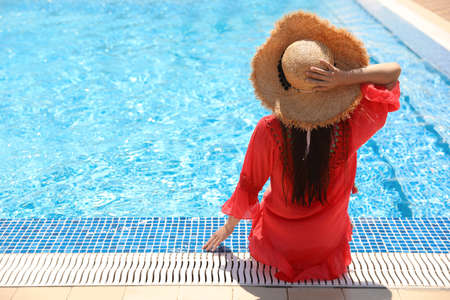 Young woman sitting near outdoor swimming pool, back view. Space for text 스톡 콘텐츠