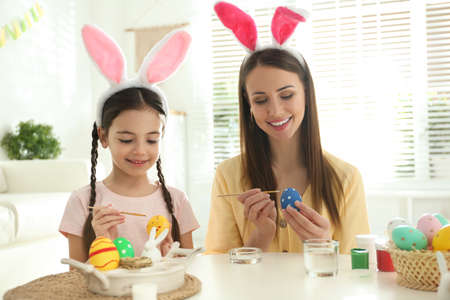 Happy mother and daughter with bunny ears headbands painting Easter eggs at home