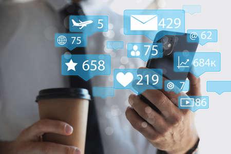 Man using modern smartphone indoors, closeup. Social media marketing