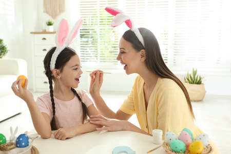Happy mother and daughter with bunny ears headbands having fun while painting Easter egg at home Stock fotó