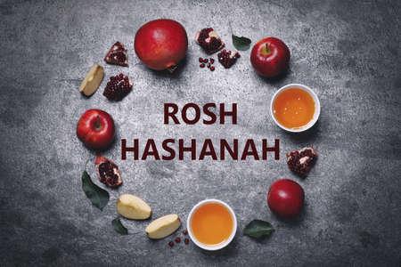 Frame of honey, apples and pomegranates on grey table, flat lay. Rosh Hashanah holiday
