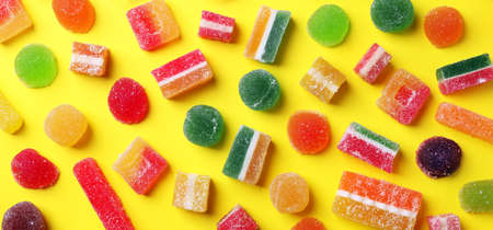 Flat lay composition with delicious colorful candies on yellow background. Banner design