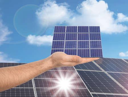 Man demonstrating solar panel outdoors, closeup. Alternative energy source 免版税图像