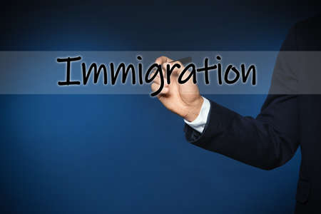 Businessman writing word IMMIGRATION on virtual screen against blue background, closeup