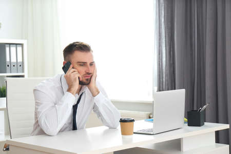 Lazy young man talking on smartphone in office