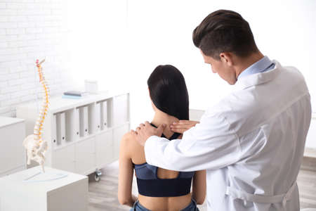 Professional orthopedist examining woman in medical office