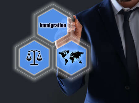 Businessman pointing at different icons on virtual screen against dark grey background, closeup. Immigration concept