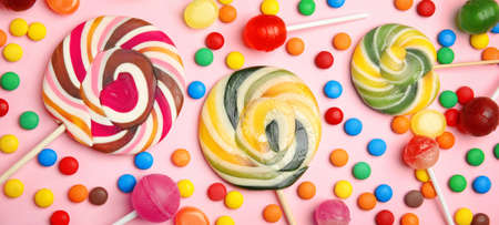 Flat lay composition with delicious colorful candies on pink background, banner design 免版税图像