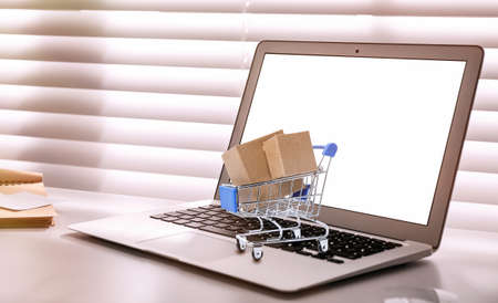 Online shopping. Small cart with boxes on laptop indoors