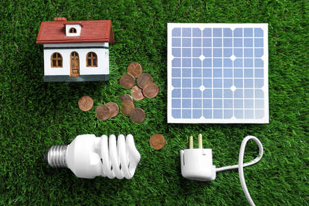 Flat lay composition with solar panel, house model, light bulb and coins on green grass 免版税图像