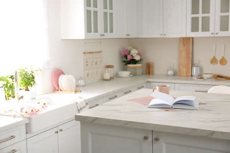 Book and cup on white marble table in modern kitchen. Interior design