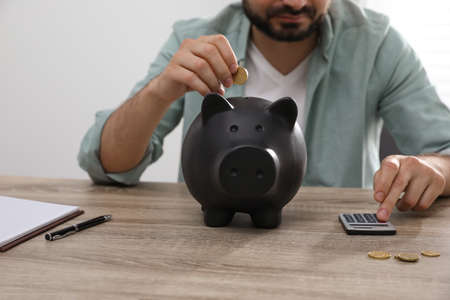 Man with calculator putting coin into piggy bank at wooden table, closeup Archivio Fotografico - 151057264