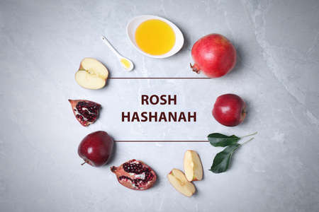 Frame of honey, apples and pomegranates on marble table, flat lay. Rosh Hashanah holiday