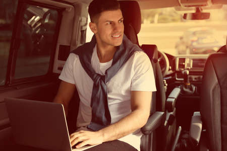 Handsome man working with laptop on backseat of modern car