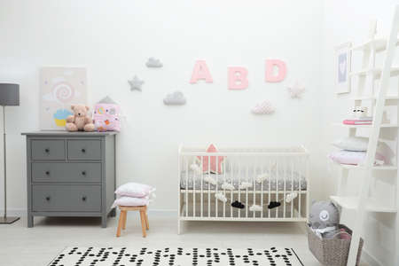 Cute baby room interior with crib and chest of drawers near white wall