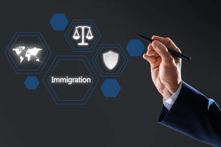 Man pointing at icons on virtual screen with pen against dark grey background, closeup. Immigration concept Imagens