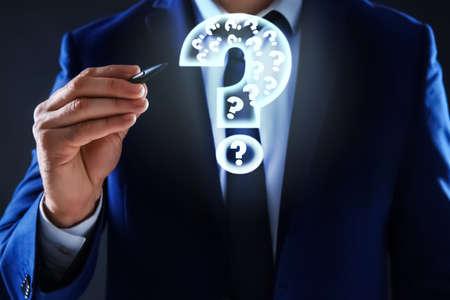 Businessman using virtual screen with question mark symbol on dark background, closeup