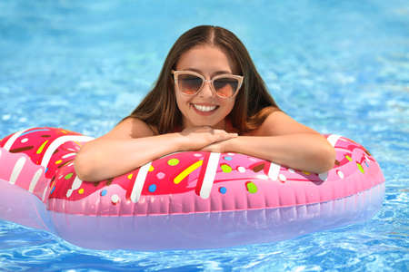Beautiful young woman on inflatable ring in swimming pool Stok Fotoğraf