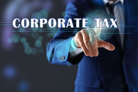 Corporate tax concept. Man touching virtual screen on color background, closeup Imagens