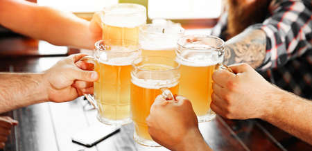 Group of friends toasting with beer in pub, closeup. Banner design