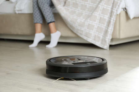 Modern robotic vacuum cleaner and blurred woman on background 免版税图像