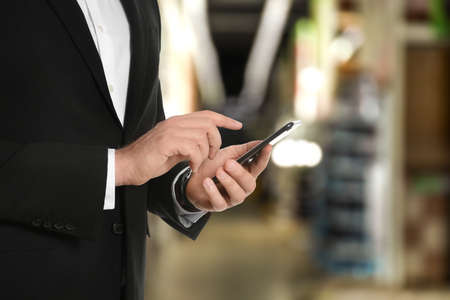 Wholesale trading. Man using WMS app on smartphone at warehouse, closeup