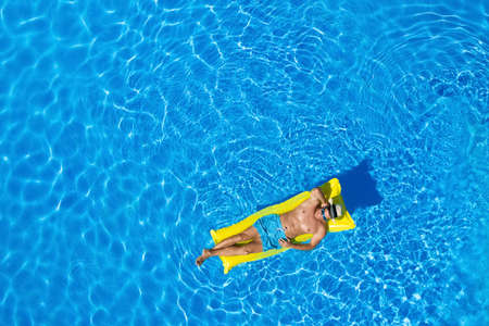 Young man with inflatable mattress in swimming pool, top view. Space for text
