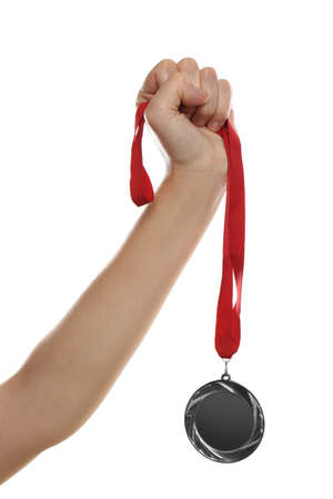 Woman holding silver medal on white background, closeup. Space for design
