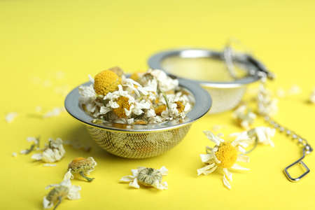 Dry chamomile flowers in infuser on yellow background, closeup